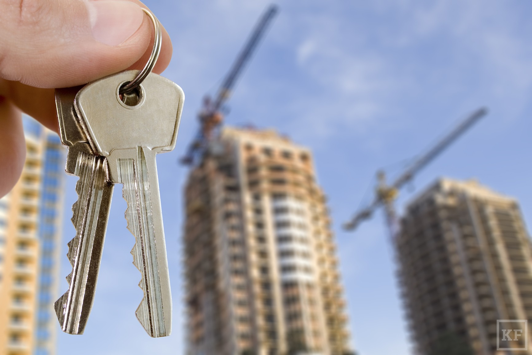 real estate concept. key in fingers with houses